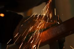 Pracownika metalu szlifierski tnący prześcieradło z ostrzarz iskrami i maszyną obrazy royalty free
