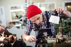 Pracownika naprawiania maszyny przy fabryką zdjęcie royalty free