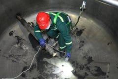 Pracownika obsiadanie wśrodku stalowego przemysłowego bojleru podczas naprawy pr Zdjęcia Stock