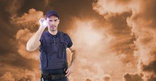 Pracownika ochrony mienia latarka przeciw niebu podczas zmierzchu Zdjęcie Royalty Free
