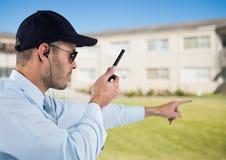 Pracownika ochrony mienia walkie talkie i gestykulować podczas gdy stojący na polu Obraz Stock