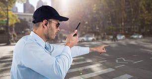 Pracownika ochrony mienia walkie talkie podczas gdy wskazujący na drodze Zdjęcie Stock