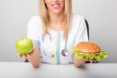 Pracownika służby zdrowia mienia hamburger i jabłko Obraz Royalty Free