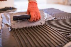 Pracownika ` s ręka stawia płytki adhezyjne ściana z ząbkowaną kielnią ceramiczne target1908_0_ płytki fotografia royalty free