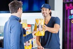 Pracownika sprzedawania popkorn Obsługiwać Przy koncesja stojakiem obrazy royalty free