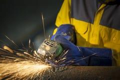 Pracownika szlifierski metal w zakładzie produkcyjnym, iskier latać Obrazy Stock