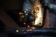Pracownika tnącego metalu fajczana używa graniasta szlifierska maszyna zdjęcie stock