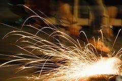 Pracownika tnący metal z ostrzarzem, iskry podczas gdy szlifierski żelazo Depresji Kluczowa fotografia obraz royalty free