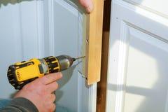 Pracownika use świder naprawiać furnitureand musztruje gabinetowego drzwi Fotografia Royalty Free