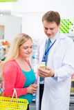 Practical advice. Vertical image of a pharmacist giving practical advice to the client on the foreground stock photography