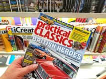 Practical Classics magazine in a hand. AMSTERDAM, NETHERLANDS: - OCTOBER 8, 2018: Practical Classics magazine in a hand over a stack of magazines. Practical royalty free stock photos