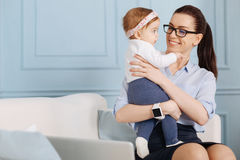 Practical experienced specialist enjoying her maternity leave. Gentle and caring. Accomplished energetic young women sitting on a couch and spending her break royalty free stock image