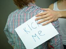 Practical joke. Guy being unaware of a �Kick me� sign attached to his back royalty free stock photos