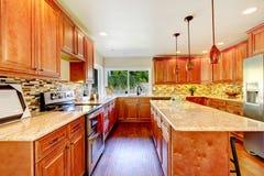 Practical kitchen with storage combination and granite tops. Practical kitchen with storage combination, tile back splash trim, kitchen island, pendant lights stock images