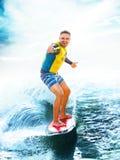 Practicando surf, océano azul Pulgares de la demostración del hombre joven para arriba en wakeboard imágenes de archivo libres de regalías
