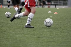 Practice. Balls and legs on a soccer/football field Royalty Free Stock Photography
