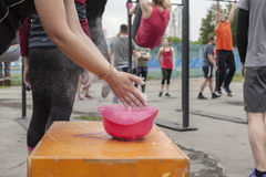 Practice crossfit in the Park. An athlete before exercise with a barbell rubs his hands with chalk Royalty Free Stock Photos