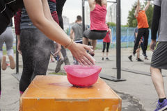 Practice crossfit in the Park. An athlete before exercise with a barbell rubs his hands with chalk Stock Photography