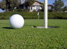 Practice Green. A golf ball near the cup on a practice green, clubhouse in the background Royalty Free Stock Photo