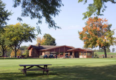Practice Green And Clubhouse. Golf course practice green and clubhouse pro shop with carts ready to go. A picnic table is provided for a rest stop. Great autumn Stock Photo