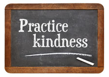 Practice kindness on blackboard. Practice kindness - inspirational advice on a vintage slate blackboard Stock Image