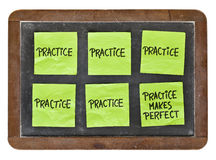 Practice makes perfect concept. Green sticky notes with black handwriting on a vintage slate blackboard Royalty Free Stock Photography