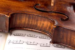 Practice makes perfect (landscape). A dusty old violin rests sideways across a musical score. Only one line of the music is in focus Royalty Free Stock Photo