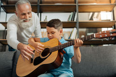 Loving grandfather and grandson having guitar practice Stock Images