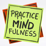 Practice mindfulness reminder note. Practice mindfulness reminder - handwriting on an isolated sticky note Stock Image