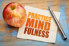 Practice mindfulness word abstract. Practice mindfulness - motto or resolution on a napkin with an apple Royalty Free Stock Images