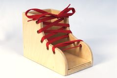 Practice Shoe. A children's wooden practice shoe with bright red laces, placed on a white background stock image