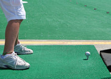 Practice Tee. A golf ball and feet at a driving range Royalty Free Stock Images