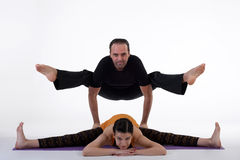 Practicing acro yoga exercises in group. People doing yoga exercises in studio on white background. Stock Photos