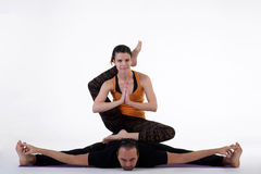 Practicing acro yoga exercises in group. People doing yoga exercises in studio on white background. Stock Image