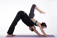 Practicing acro yoga exercises in group. People doing yoga exercises in studio on white background. Stock Photo