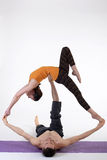 Practicing acro yoga exercises in group. People doing yoga exercises in studio on white background. Royalty Free Stock Photos