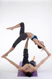 Practicing acro yoga exercises in group. People doing yoga exercises in studio on white background. Royalty Free Stock Images