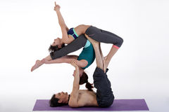 Practicing acro yoga exercises in group. People doing yoga exercises in studio on white background. Stock Photography