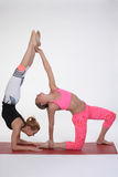 Practicing acro yoga exercises in group. People doing yoga exercises in studio on white background. Stock Images