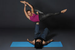 Practicing acro yoga exercises in group. People doing yoga exercises in studio on white background. Royalty Free Stock Image