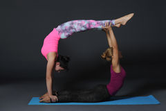 Practicing acro yoga exercises in group. People doing yoga exercises in studio on white background. Royalty Free Stock Photography