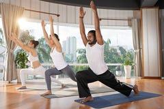 Practicing asana. Asian people practicing asana in health club Stock Image