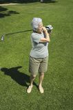 Practicing golf. Senior attractive woman practicing golf Royalty Free Stock Images