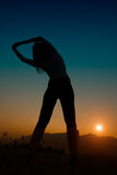 Practicing gymnast girl at sunset towards the sun stock images