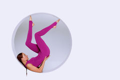 Practicing gymnastic exercises in geometric  design of round sha. Stylish and sporty woman  practicing gymnastic exercises in geometric  design of round shapes Stock Images
