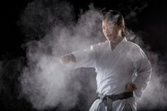 Practicing karate. Japanese sportswoman practicing karate alone Royalty Free Stock Photos