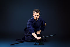 Practicing kendo. Handsome young man practicing kendo. Over dark background Royalty Free Stock Image