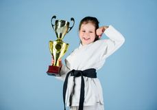 Practicing Kung Fu. happy childhood. small girl with champion cup. martial arts. sport success in single combat. winner. Girl in gi sportswear. knockout. energy stock photography