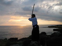 Practicing martial arts. Silhouette of a an practicing martial arts outdoors with a sword and with typical japanese clothes Stock Images