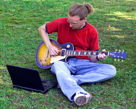 Practicing Musician. A musician practices his guitar with the help of his laptop Stock Photos